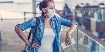 COVID-19 worldwide borders closures.Traveler with face mask stuck in airport terminal after being denied entry to other countries. Passenger stranded in airport on his travel back to home country.
